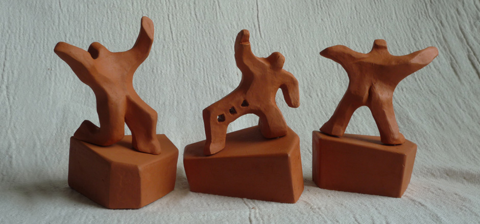 Three male figures adopt energetic postures. Terra Cotta ,height 12cm overall