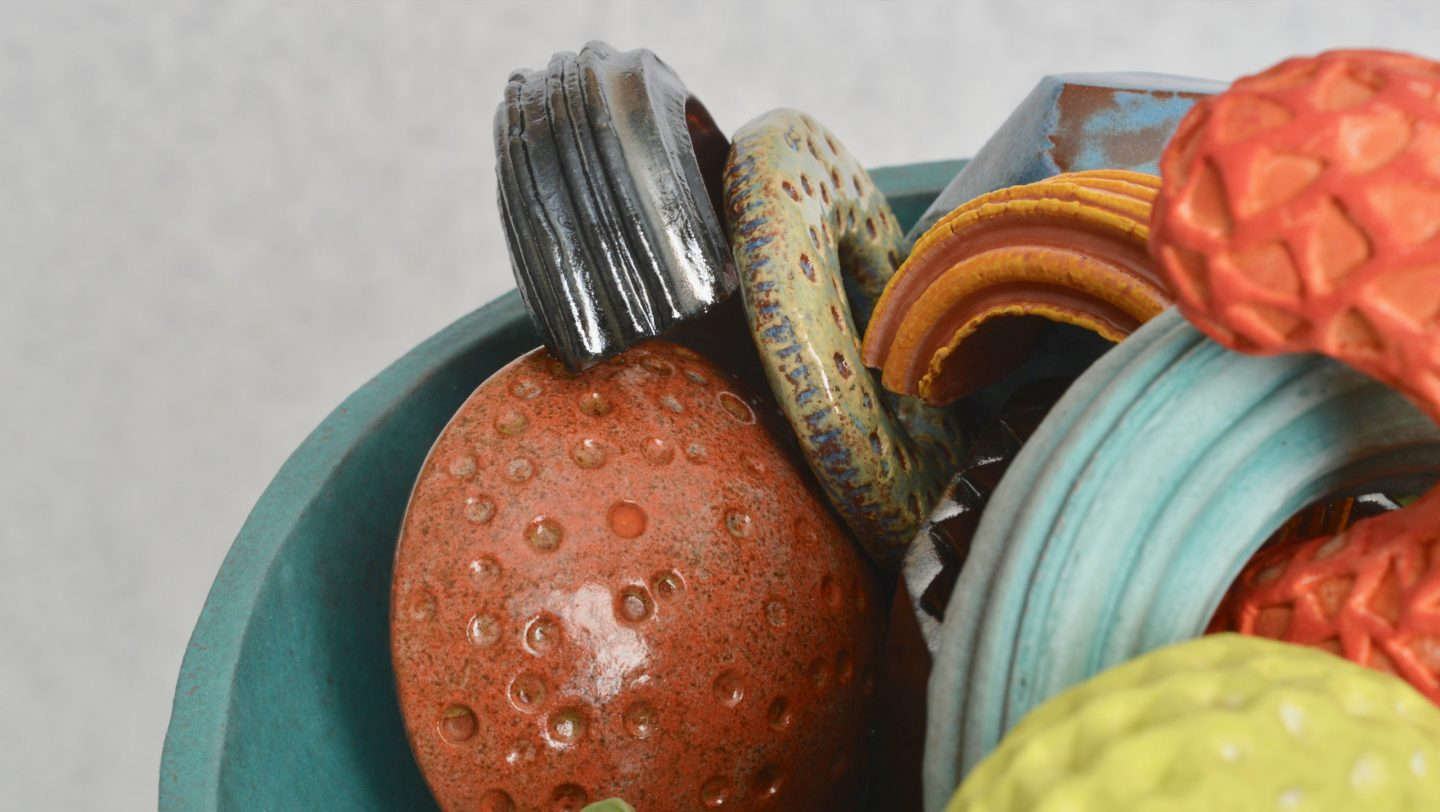 One more detail of Cornucopia - a ceramic still-life by artist Simon Fell. Shot of a group of highly coloured geometric objects in a bowl on a stand