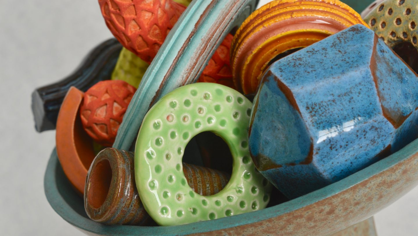 Further detail of Cornucopia - a ceramic still-life by artist Simon Fell. Shot of a group of highly coloured geometric objects in a bowl on a stand