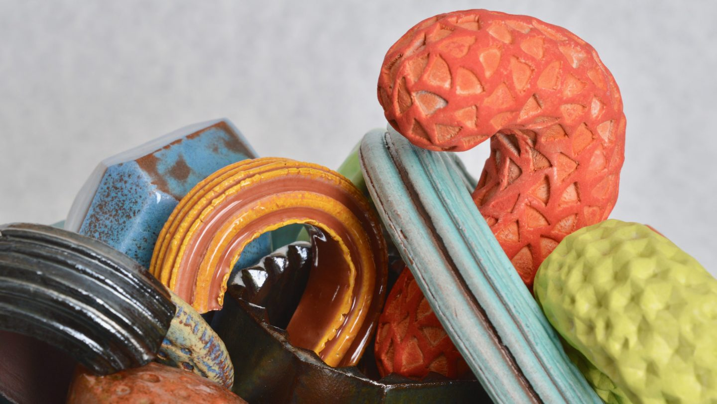 Another detail shot of Cornucopia - a ceramic still-life by artist Simon Fell. A group of highly coloured geometric objects in a bowl on a stand
