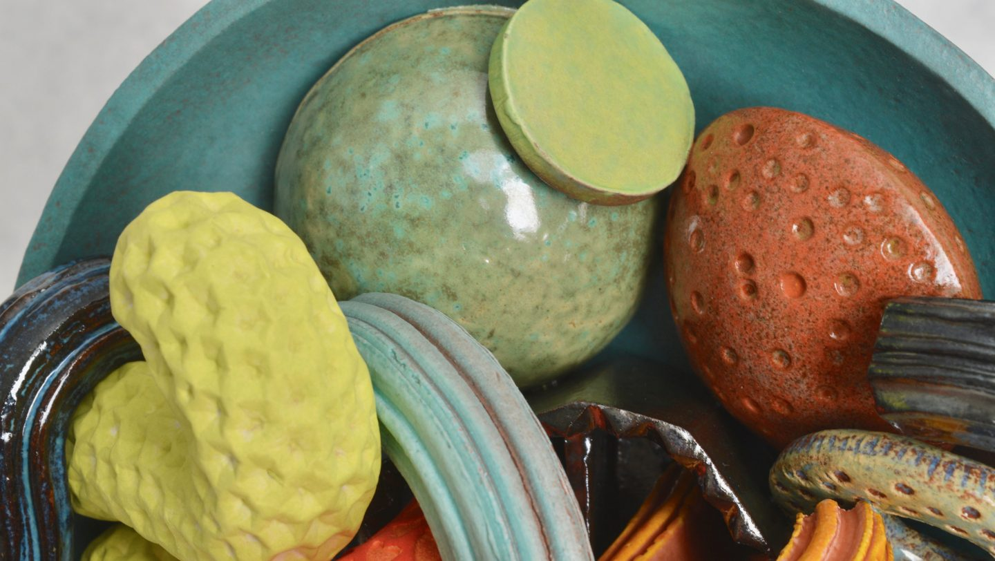 Detail of Cornucopia - a ceramic still-life by artist Simon Fell. Shot of a group of highly coloured geometric objects in a bowl on a stand