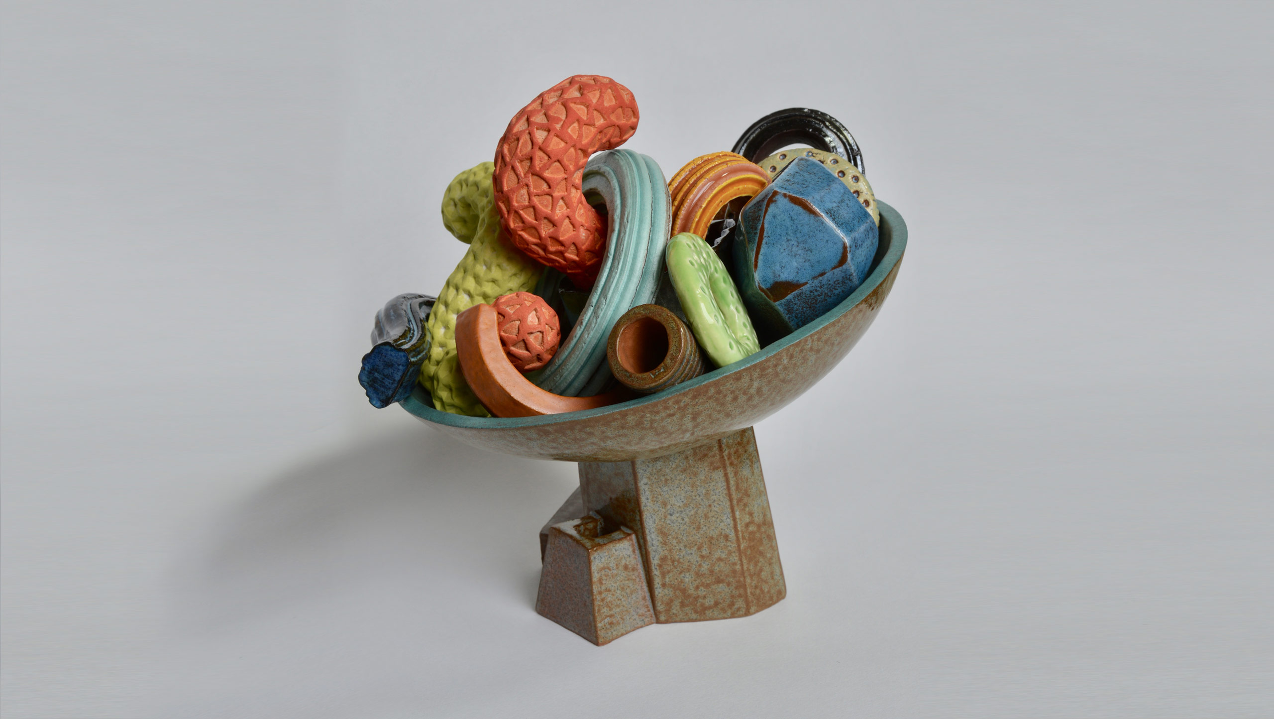 Cornucopia,a ceramic still-life, an assemblage of richly textured and coloured geometric and curvaceous objects