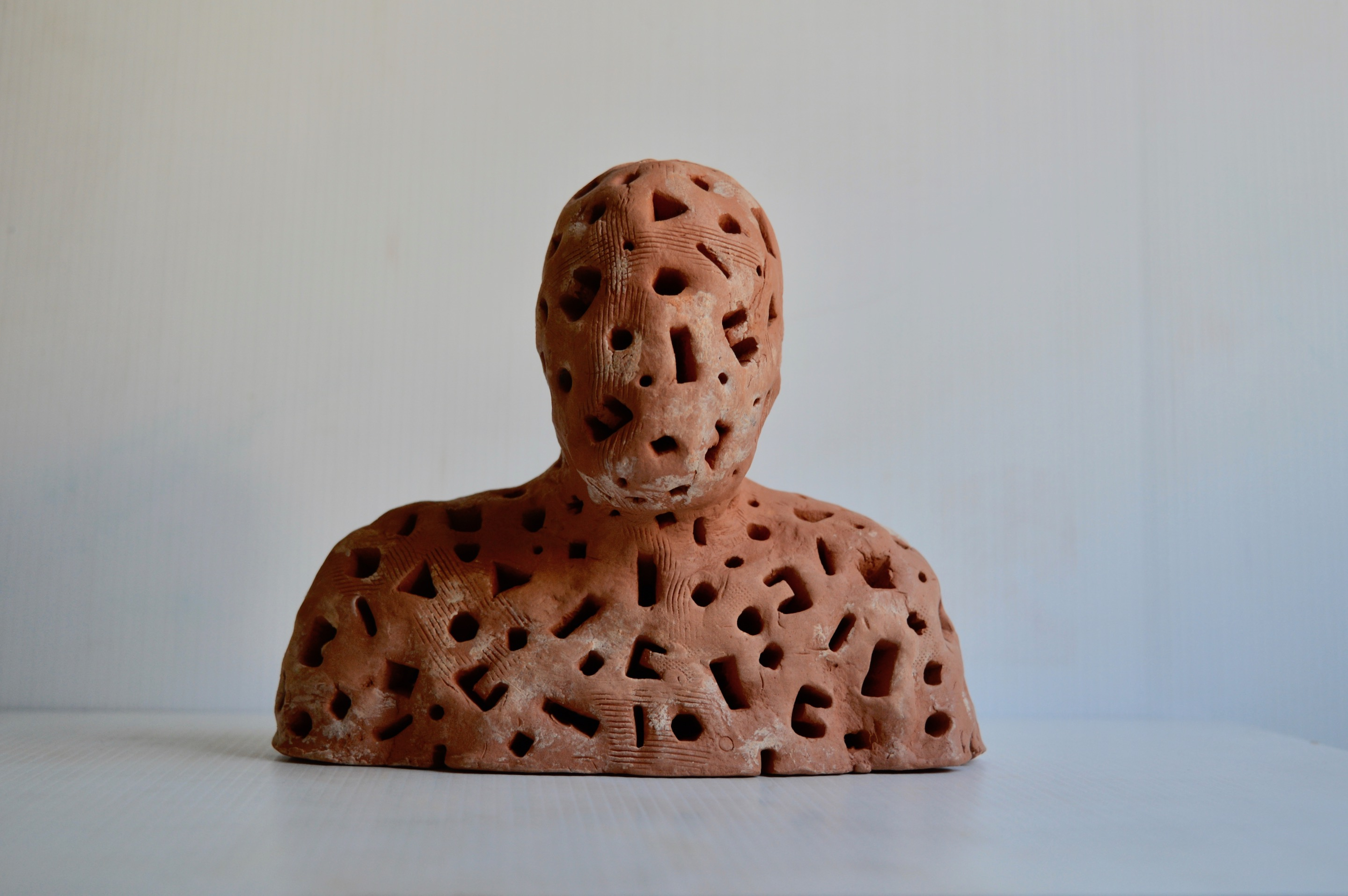 A semi-solid bisque fired terracotta figure 15cm wide which is part of a developing installation of 13 or more figures in glazed and unglazed terra-cotta, plaster and papier mache illuminated by LED lights on stands made of cardboard and mdf