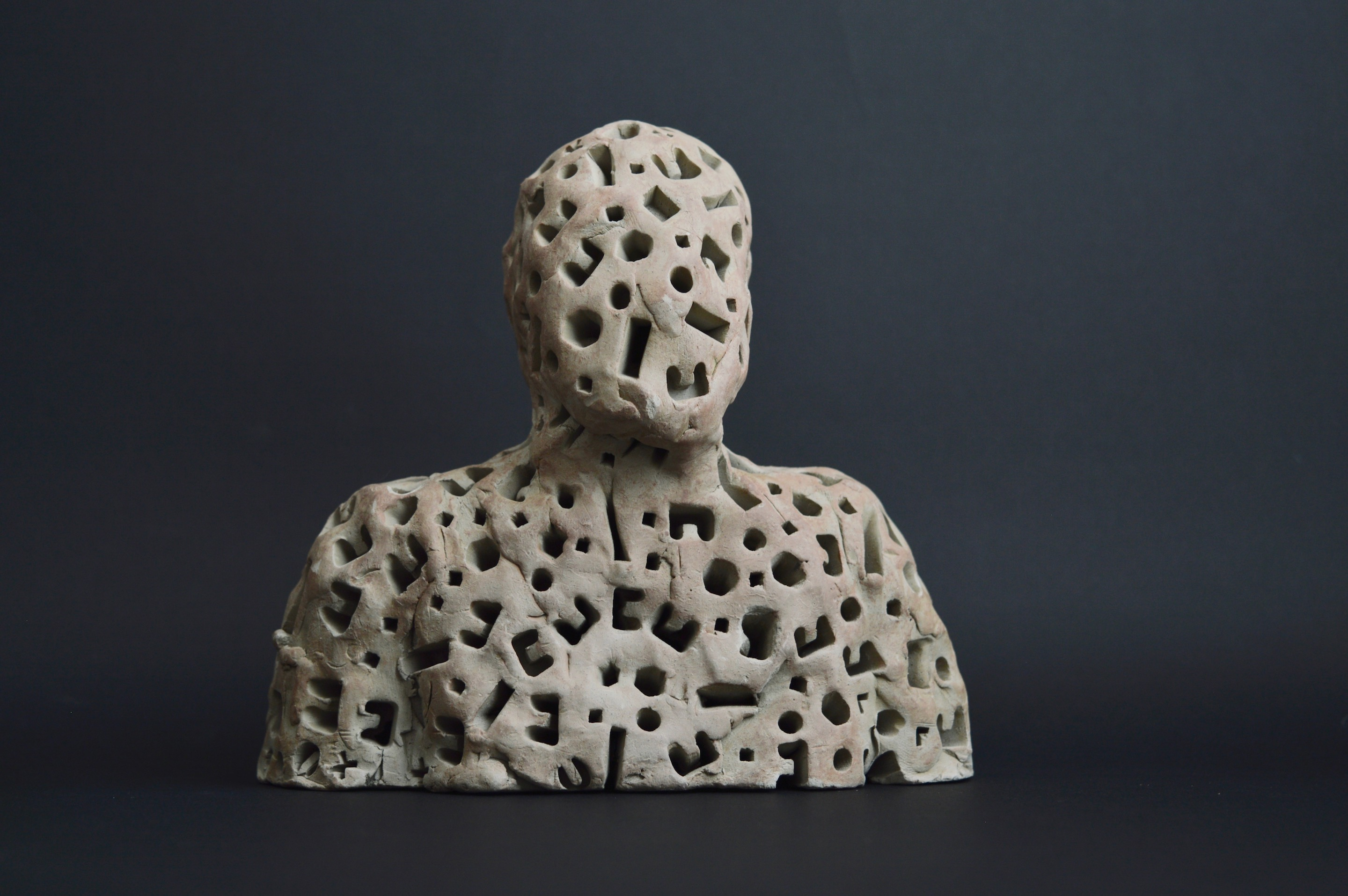 A semi-solid unfired buff clay figure 15cm wide which is part of a developing installation of 13 or more figures in glazed and unglazed terra-cotta, plaster and papier mache illuminated by LED lights on stands made of cardboard and mdf