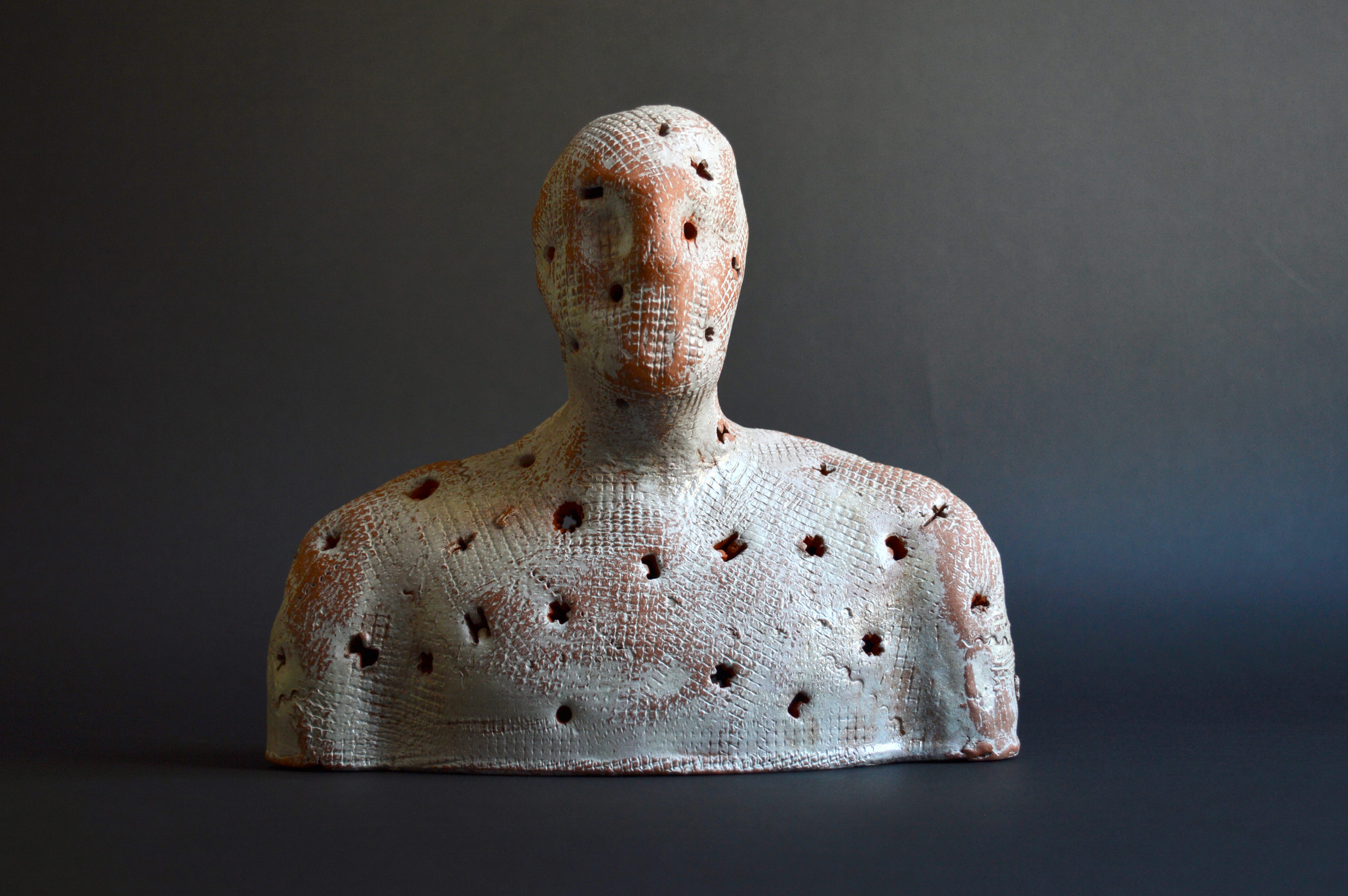 A glazed terra cotta figure 20cm wide which is part of a developing installation of 13 or more figures in glazed and unglazed terra-cotta, plaster and papier mache illuminated by LED lights on stands made of cardboard and mdf