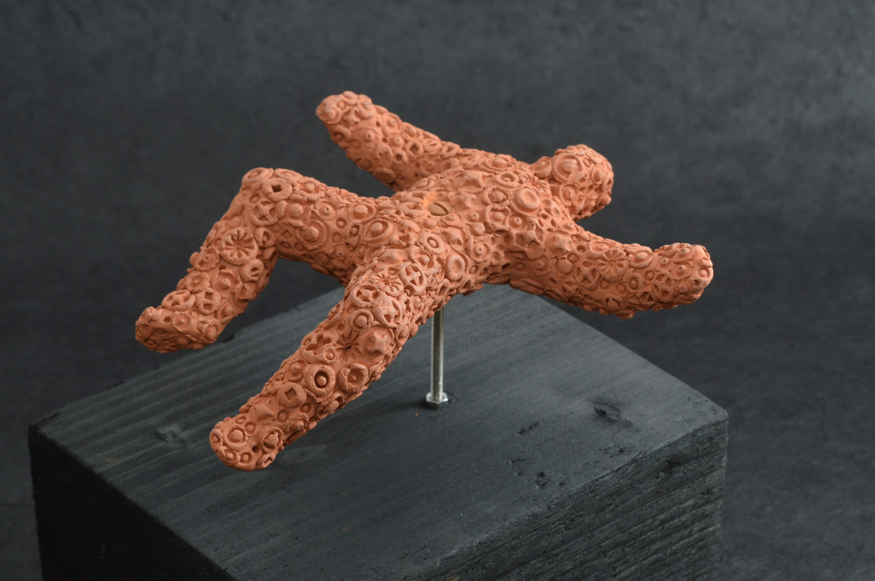 Falling Figure 02 - after Madmen, an unglazed terracotta figure about 10cm in length encrusted with embossed forms