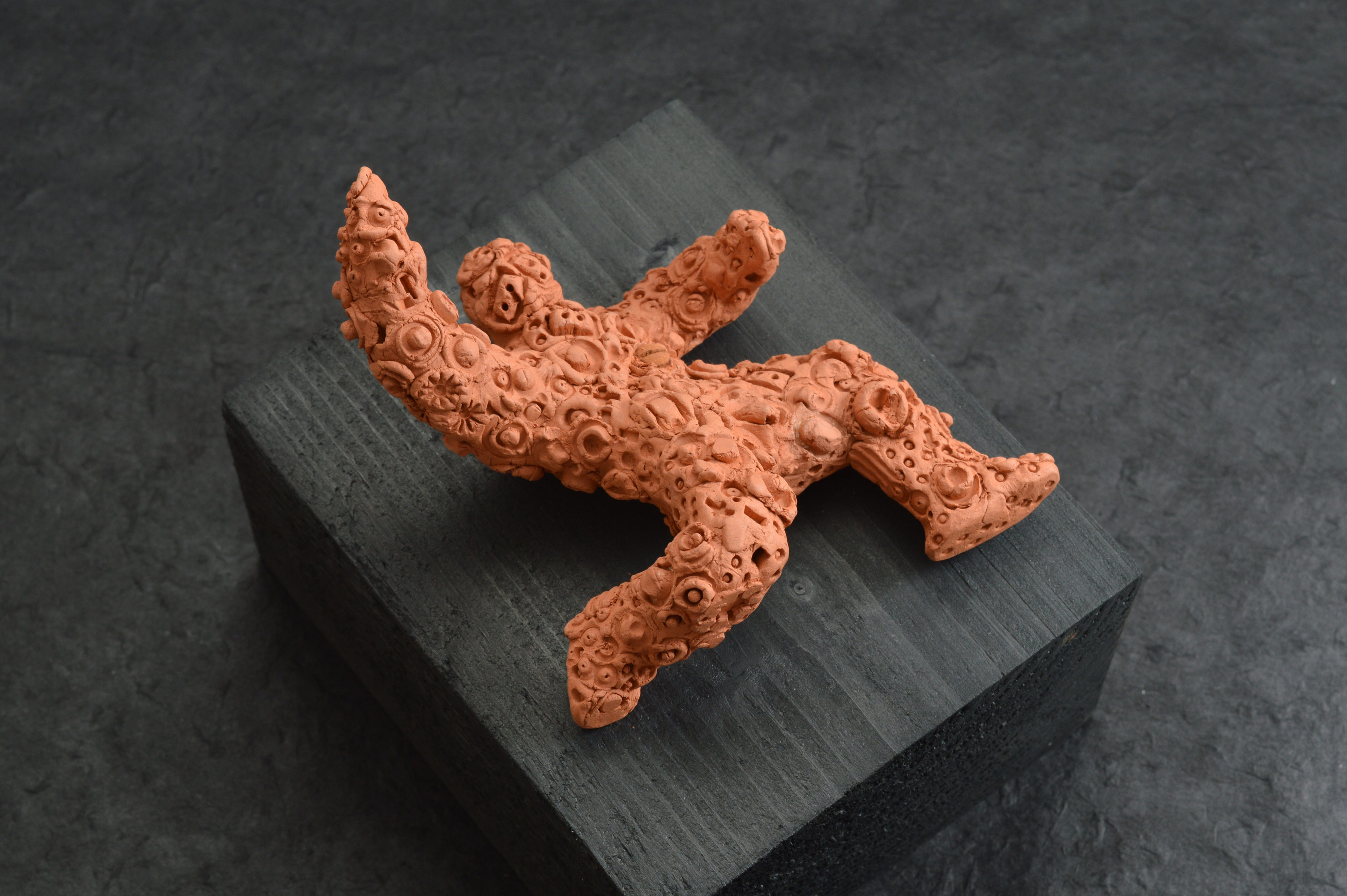 Falling Figure 01-operatic, an unglazed terracotta figure about 10cm in length encrusted with embossed forms