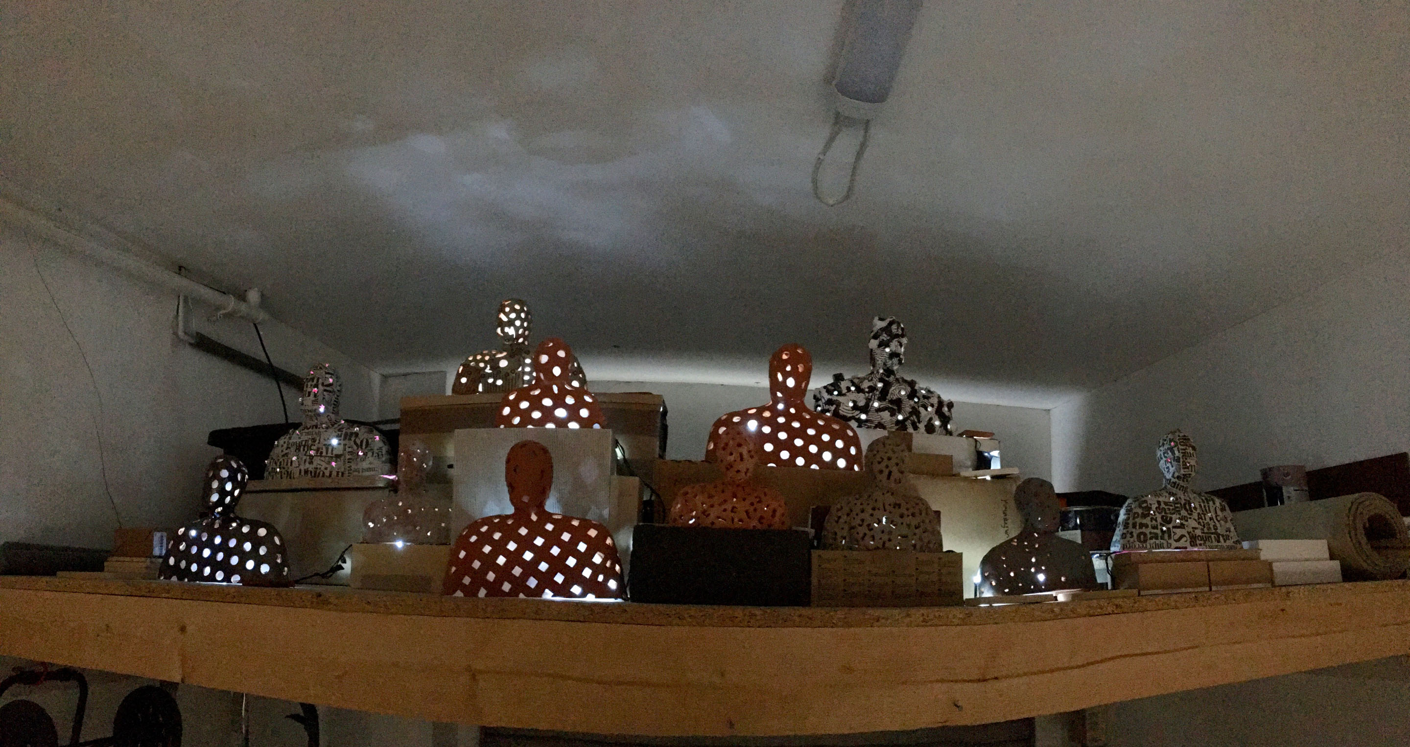 A panorama view of a developing installation of 13 or more figures in glazed and unglazed terra-cotta, plaster and papier mache illuminated by LED lights on stands made of cardboard and mdf