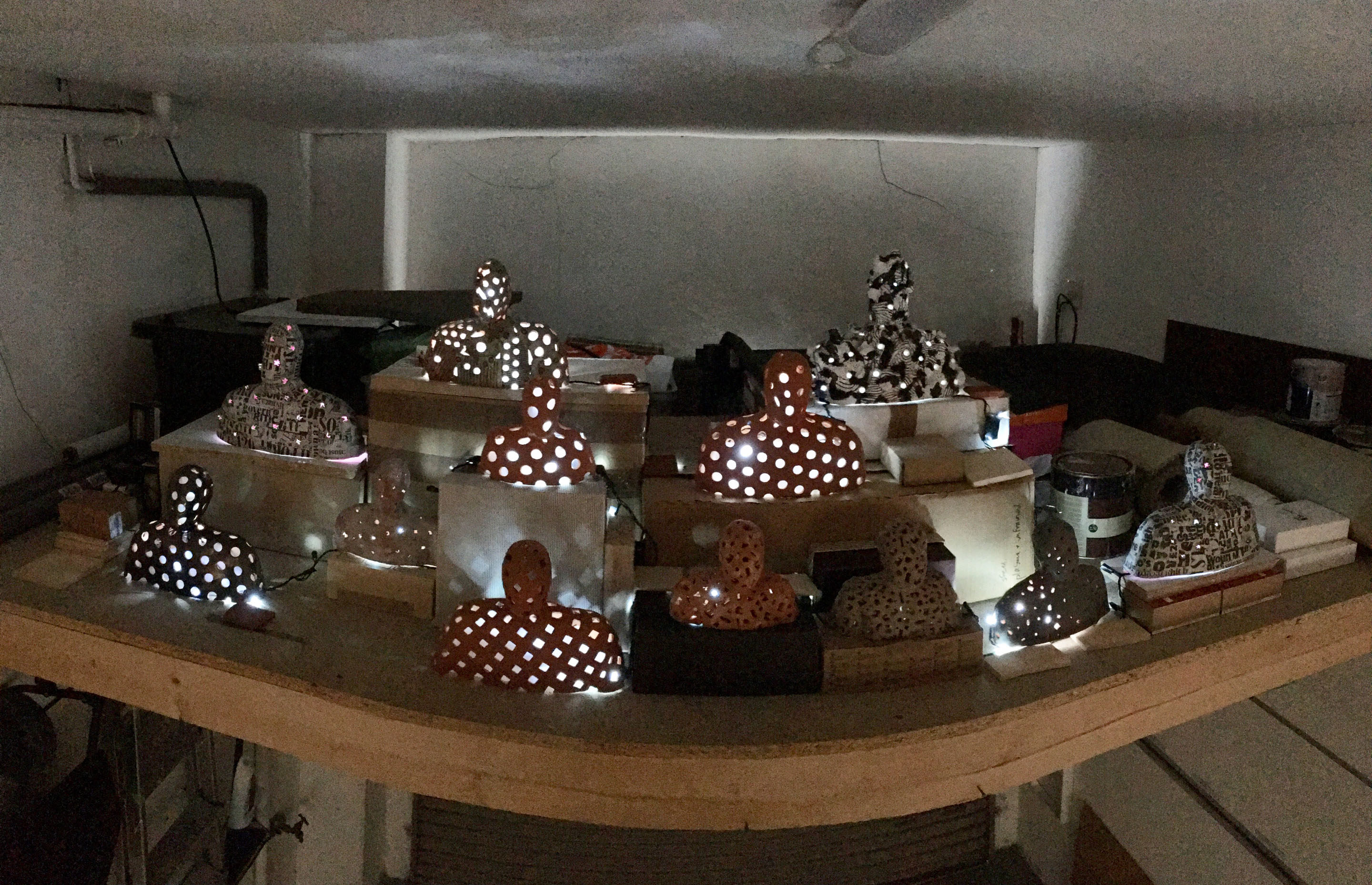 A panorama view of a developing installation of 13 or more figures in glazed and unglazed terra-cotta, plaster and papier mache illuminated by LED lights on stands made of cardboard and mdf. As shown at Civilians, May 2019