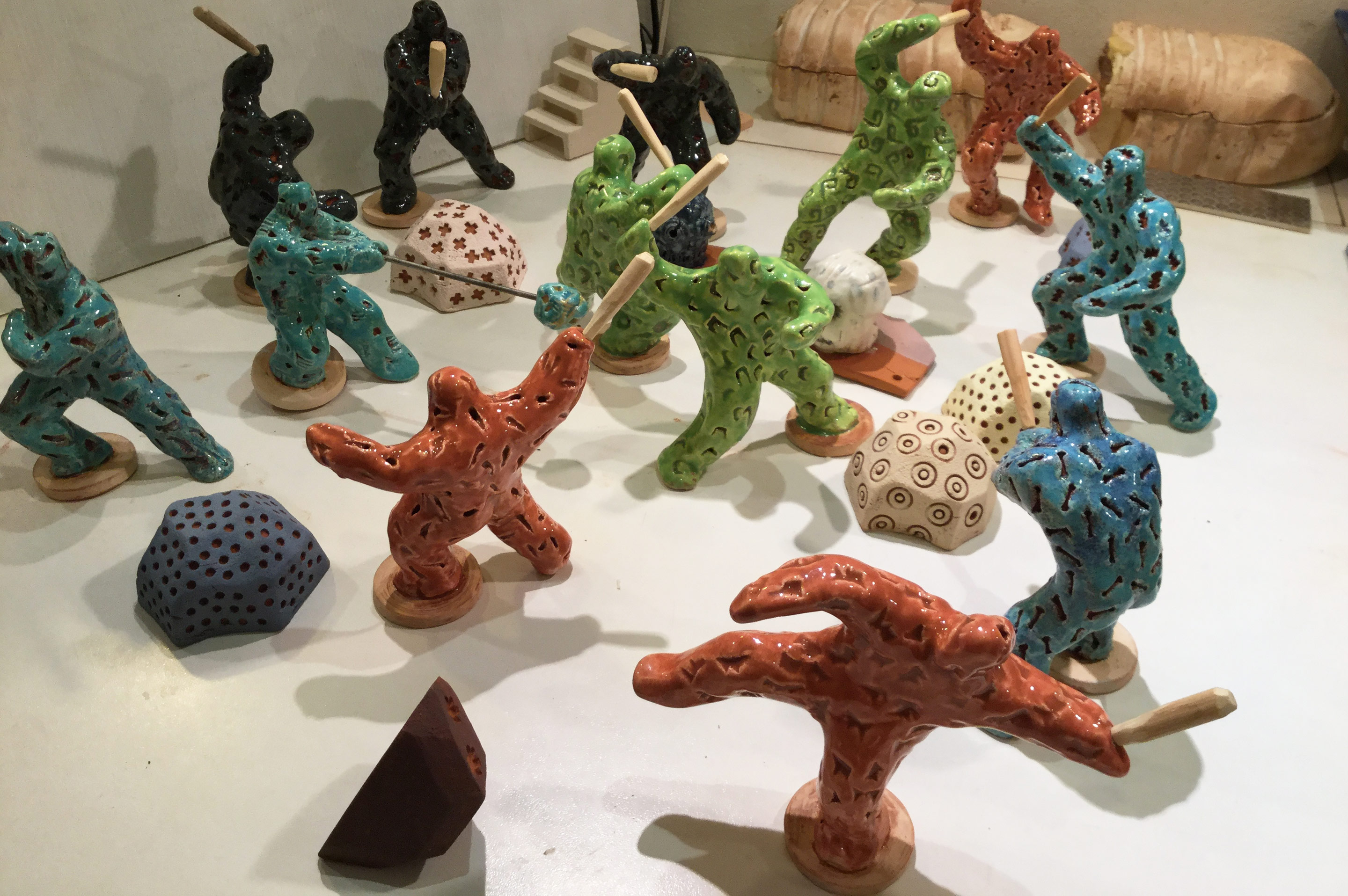 Work in progress on 'Riot of Colour' - twelve small coloured figures with clubs, figures about 10cm tall