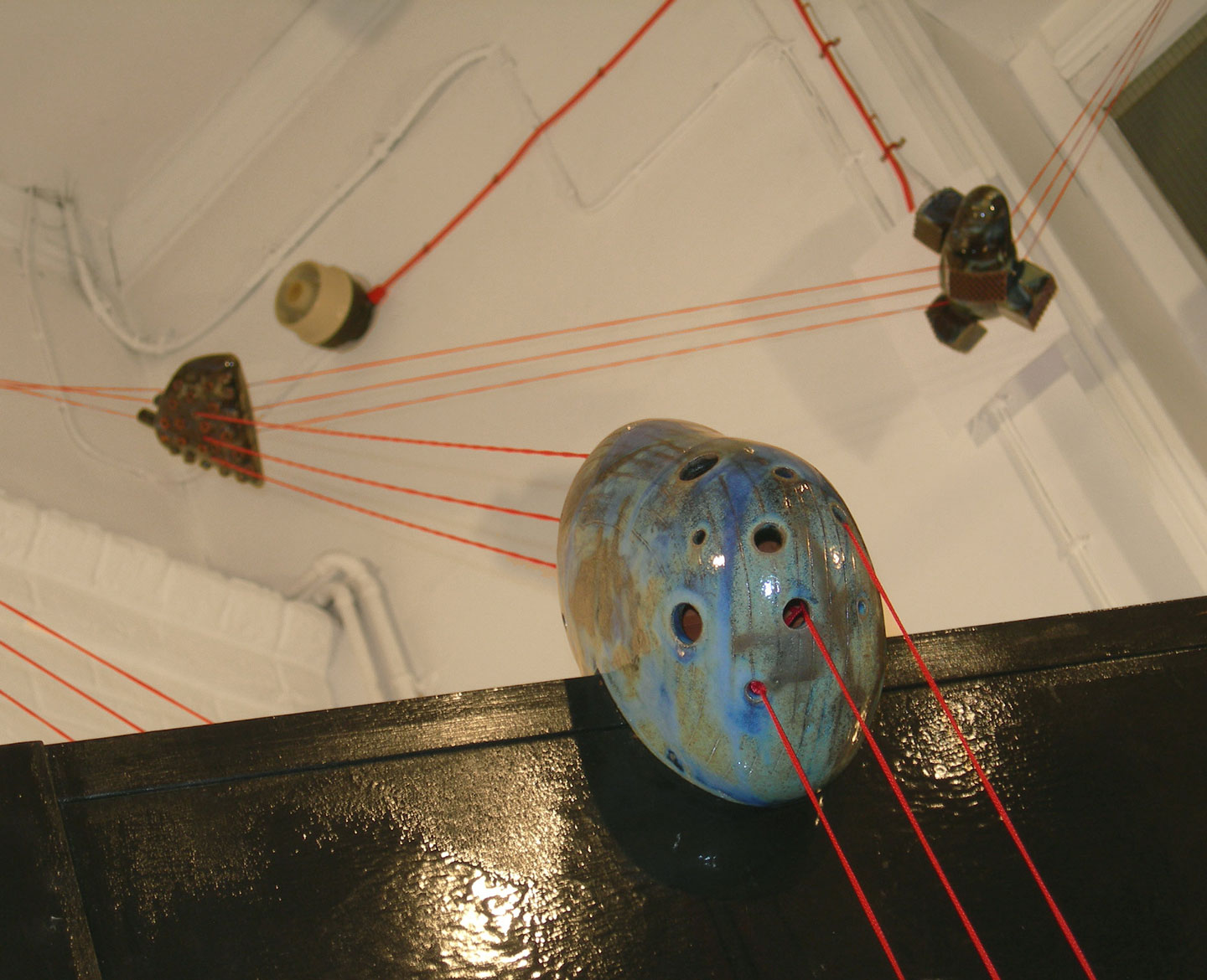 Photo of 'On the threshold of destiny' a ceramic installation of six ceramic compositions linked together with three strands of bright red cord.