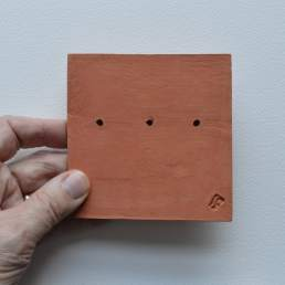 Back of tile with three faces and random square impressions